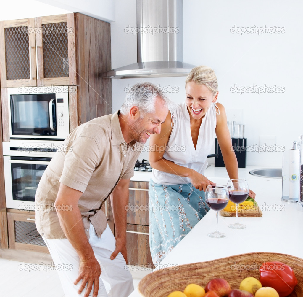 Mature woman preparing salad while her husband is having wine — Stock Photo #3332733