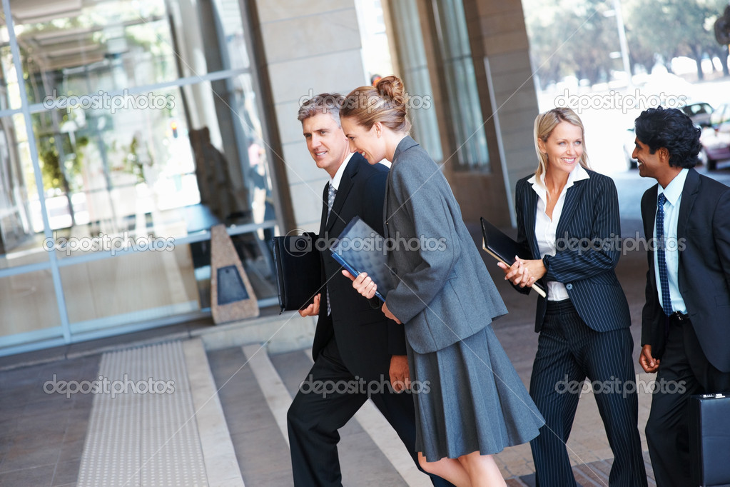 Happy team of business walking into their office building  Stock Photo #3333031
