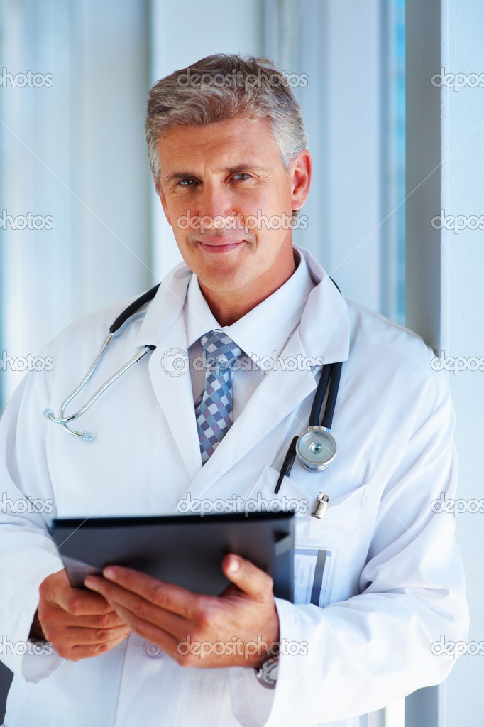 Portrait of a successful medical doctor standing in white uniform — Stock Photo #3333267