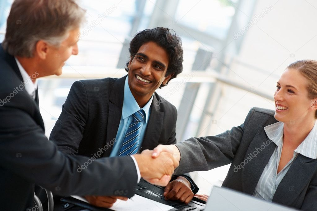 Business associates fixing a deal with a client at a meeting — Stock Photo #3334153