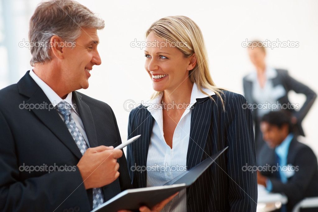 Business signing a file while speaking to his secretary — Stock Photo #3334374