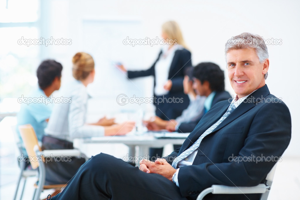 Senior business relaxed on a chair with his colleagues at a meeting in the back — Stok fotoğraf #3334479