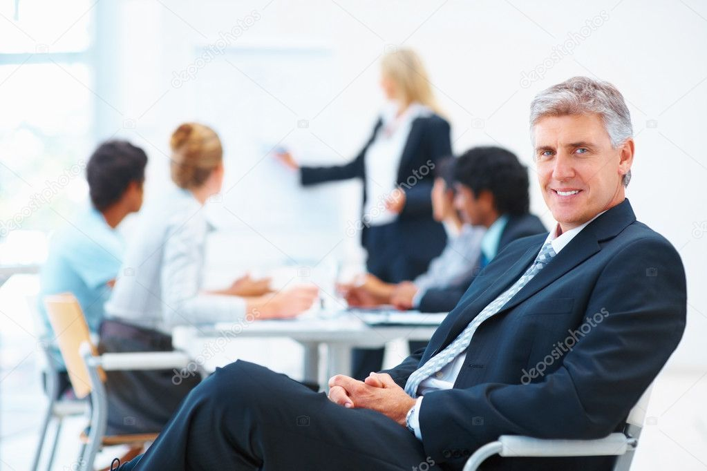 Senior business relaxed on a chair with his colleagues at a meeting in the back — Photo #3334479