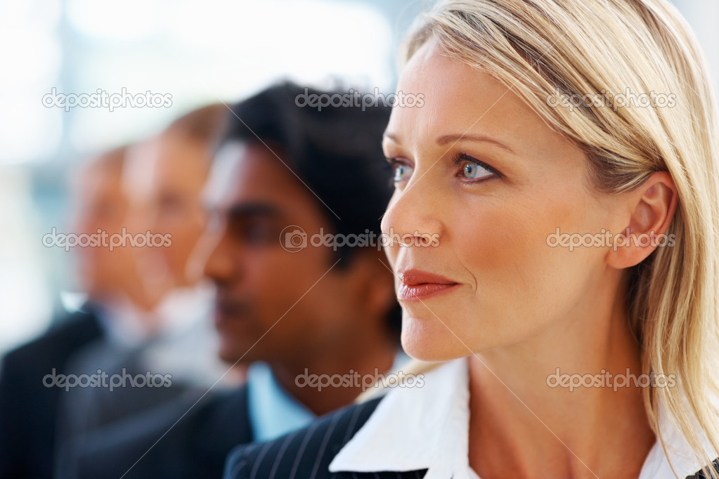 Closeup of a young business woman in line with her colleagues, looking away — Stock Photo #3334697