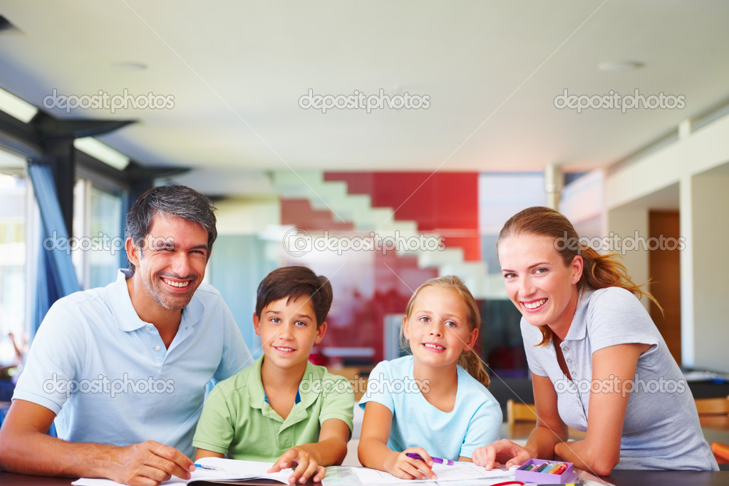 Loving parents assisting their children with their schoolwork  Stock Photo #3335560