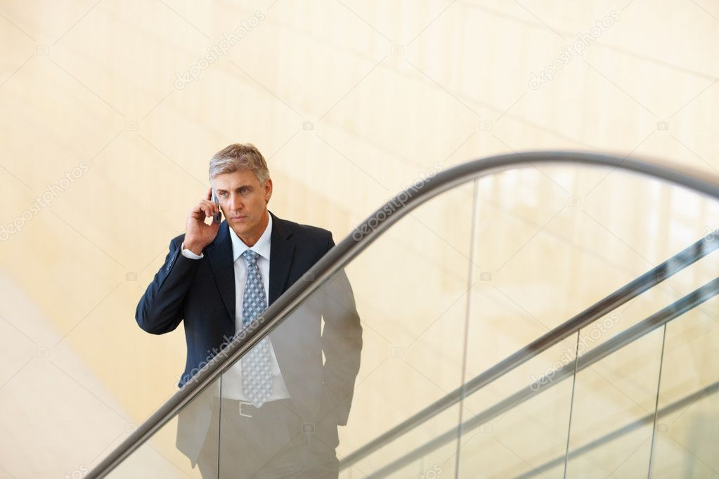 An aged business man communicating on cell phone on an escalator  Stock Photo #3335871