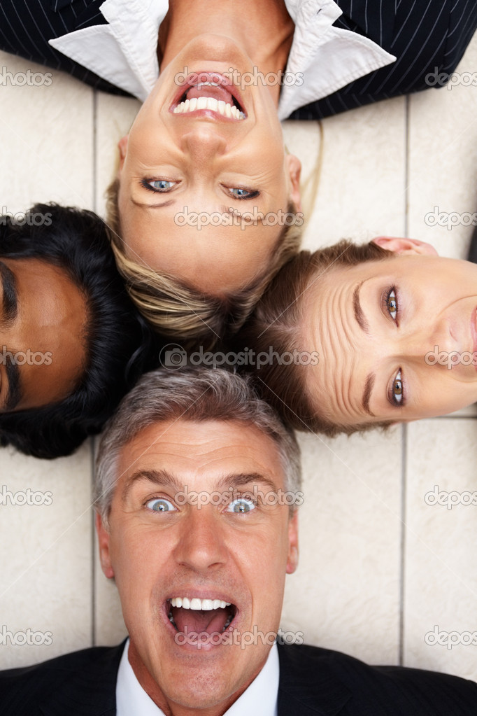 Portrait of cheerful business lying on floor with heads together — Stock Photo #3335954