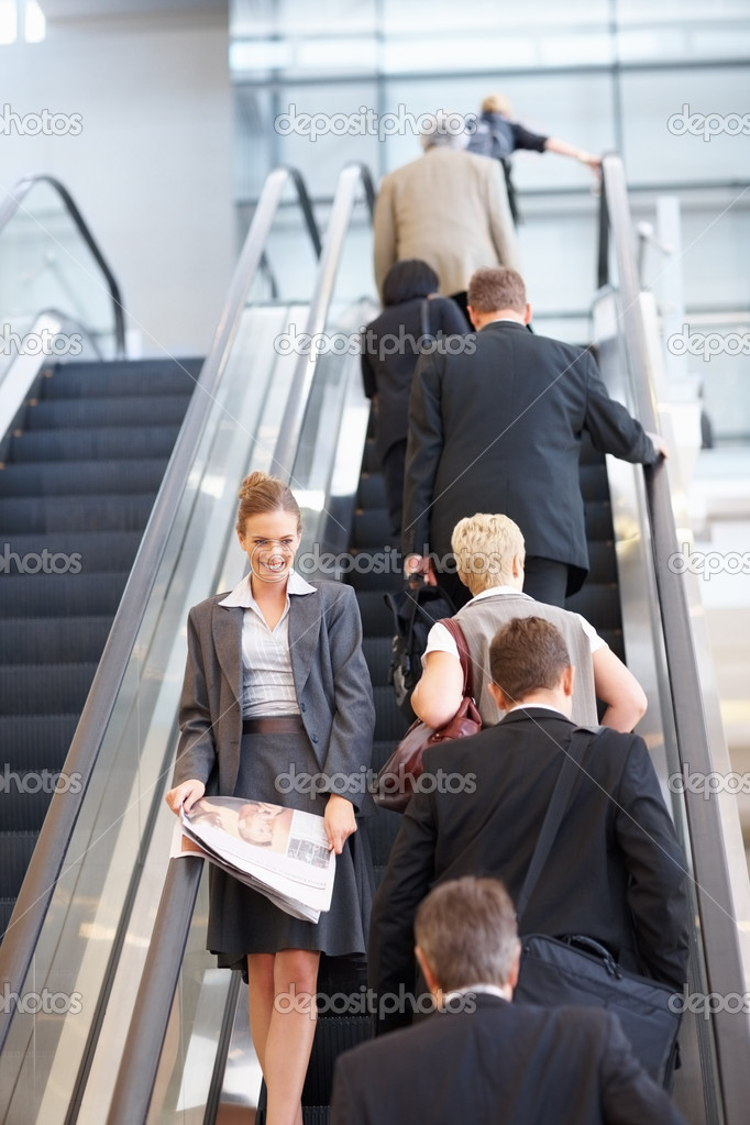 Business colleagues using the escalator, focus on business woman — Stock Photo #3335966