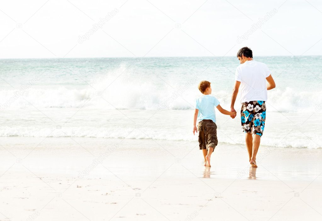 Rear view of a father and son holding hands walking towards the sea — Stock Photo #3337662