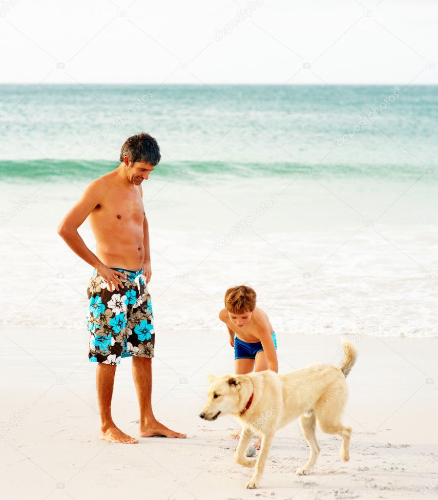 Mature man and his son at the sea shore playing with a dog — Stock Photo #3337988