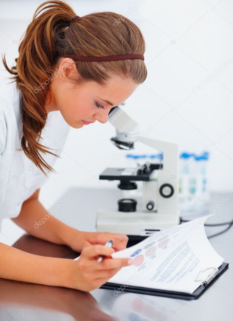 Pretty young female scientist going through her notes while working on a microscopic sample — Stock Photo #3338333