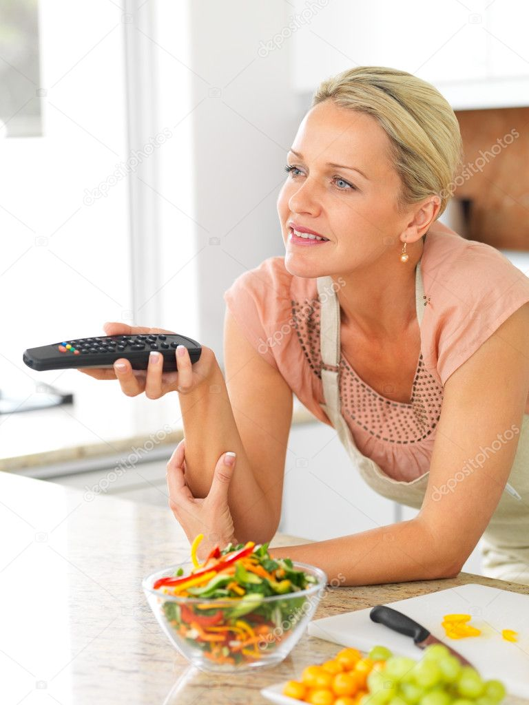 depositphotos 3339243 Middle aged woman with the TV remote while preparing dinner in t Beautiful mature in the kitchen watching television while preparing salad