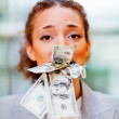 Unhappy young business woman with money in her mouth - Stock Photo