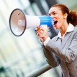 Young business woman screaming in to a megaphone - Stock Photo