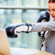 Young business woman in fighting position at work, wearing boxin - Stock Photo