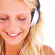 Royalty-Free Stock Photo: Happy female listening pleasantly to music on headphones
