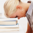 Royalty-Free Stock Photo: Tensed young female student with head on a stack of books
