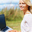 Royalty-Free Stock Photo: Cute young woman using a laptop at the park