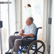 Royalty-Free Stock Photo: Elder man sitting on a wheelchair at the hospital