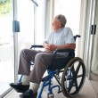 Handicapped elderly man sitting isolated at a hospital - Stockfoto