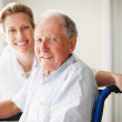 Royalty-Free Stock Photo: Happy retired man on the wheel chair with a nurse