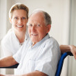 Happy old man on the wheel chair with a nurse - Stock Photo