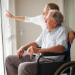 Royalty-Free Stock Photo: Old man on a wheelchair , nurse pointing outside