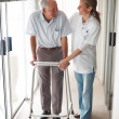 Royalty-Free Stock Photo: Happy senior patient being assisted by a doctor to walk
