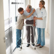 Royalty-Free Stock Photo: Young boy hugging grandfather at the corridor of a hospital