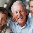 Old man laughing with daughter and grandson - Stock Photo