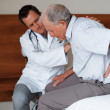 Royalty-Free Stock Photo: Doctor treating a senior man with backache