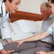 Hospital staff assisting an elderly man into bed - Stock Photo