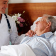 Royalty-Free Stock Photo: Young doctor visiting a senior patient at his bed