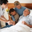 Happy senior patient being visited by family at the hospital - Stock Photo