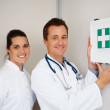 Happy doctors with a first aid kit up on the wall at hospital - Stockfoto