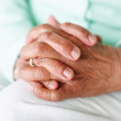 Closeup focus of a senior woman's hand joined together - Stock Photo
