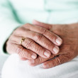 Closeup focus of an elderly woman's hand together - Stock Photo