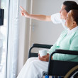 Royalty-Free Stock Photo: Old woman on a wheelchair , nurse pointing outside
