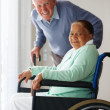 Elderly woman on a wheel chair , husband at the back - Stock Photo