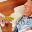 Elderly sick man being given a pill by doctor - Stock Photo