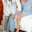 Doctor examining the reflexes of senior man , tapping on the kne - Foto Stock