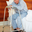 Royalty-Free Stock Photo: Sad elderly man sitting with a walker on his bed