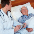 Routine checkup - Doctor making a report on an elderly patient - Foto Stock