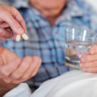 Closeup of a senior man being given a life saving pill - Stock Photo