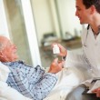 Senior patient accepting a bottle of medicine from the doctor - Stock Photo