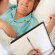 Royalty-Free Stock Photo: Happy elderly woman in bed getting a checkup a doctor