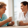 Elderly woman having a coffee with a young nurse - Photo