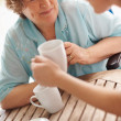 Happy senior patient having coffee with a nurse - Stock Photo