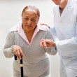 Royalty-Free Stock Photo: Young doctor helping a senior patient to walk