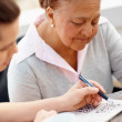 Old woman being helped by a nurse to solve a crossword puzzle - Stock Photo